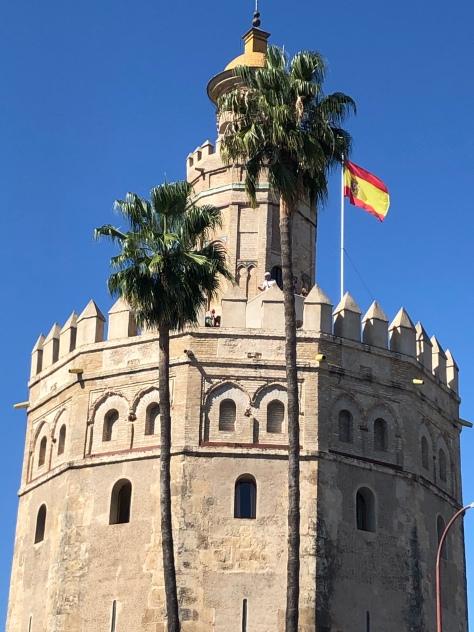 """alt=""""circular stone castle with Spanish flag"""""""